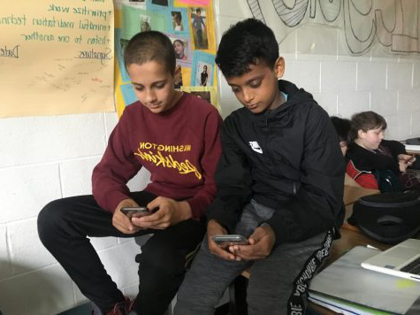 Hamza Hawa (right) and Isaac Varghese use social media during Panther Time.