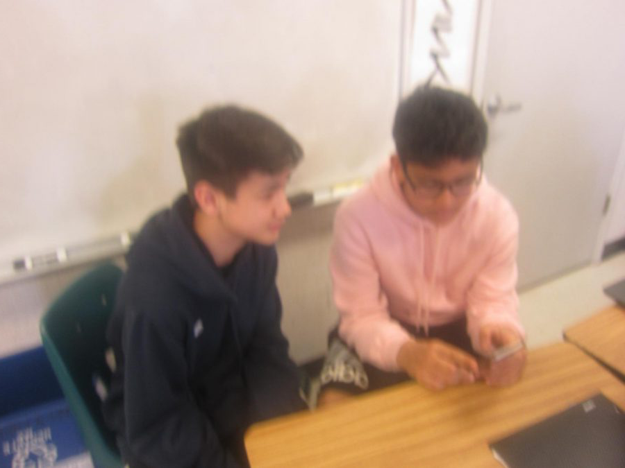 Tanishq nerkar. shows Ansel Morrill something on social media during class.